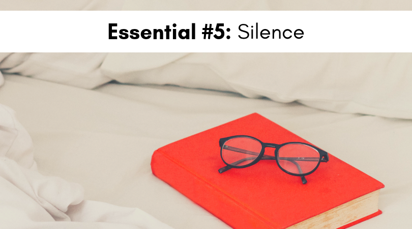 A red book with glasses sitting on the top placed on white bedsheets