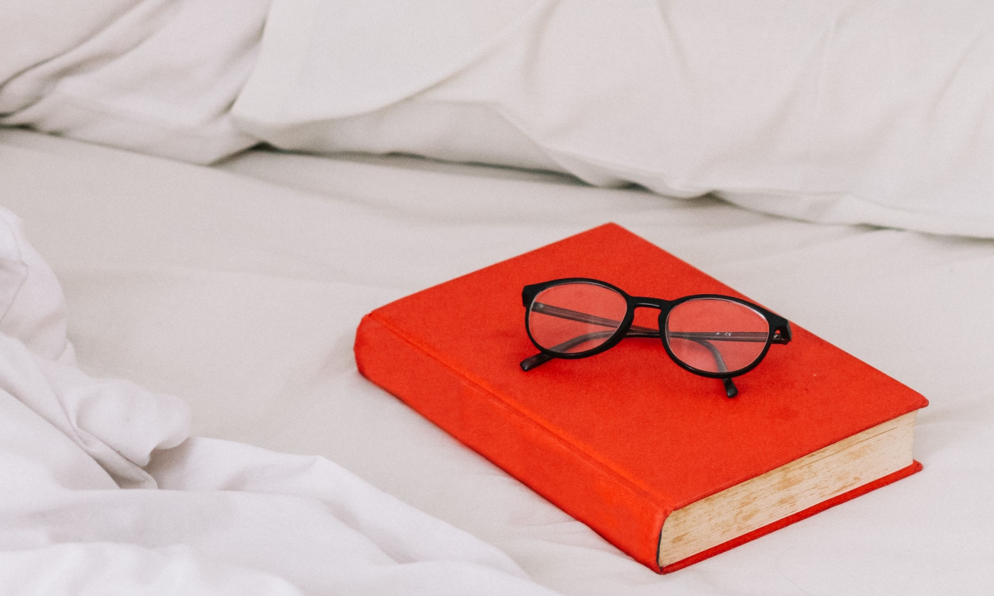 A red book with glasses on top, sitting on white bed sheets